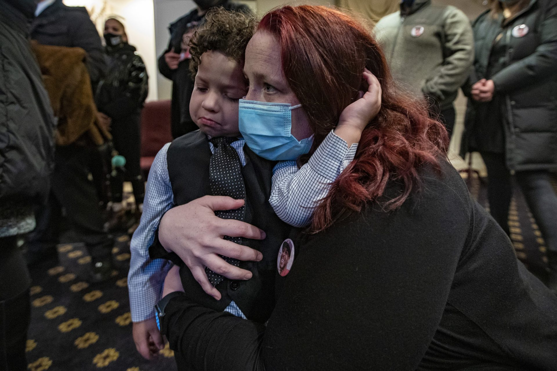 Henry Tapia's girlfriend, Courtney Morton, holds her 3-year-old son Eli during his funeral.  (Jesse Costa / WBUR)