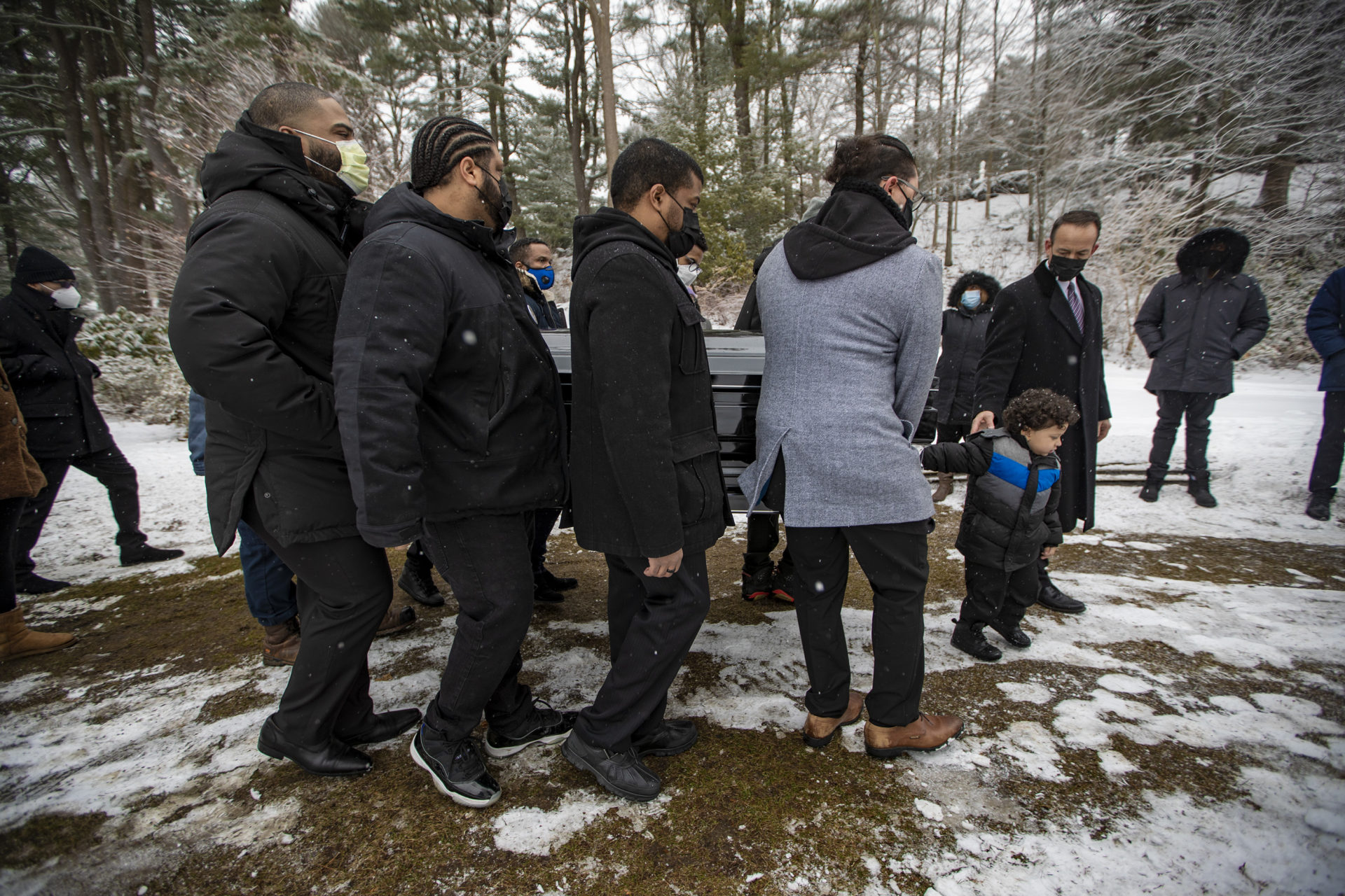 Henry Tapia's 3-year-old son Eli helps the pallbearers carry his father's coffin to the burial site at Forest Hills Cemetery.  (Jesse Costa / WBUR)