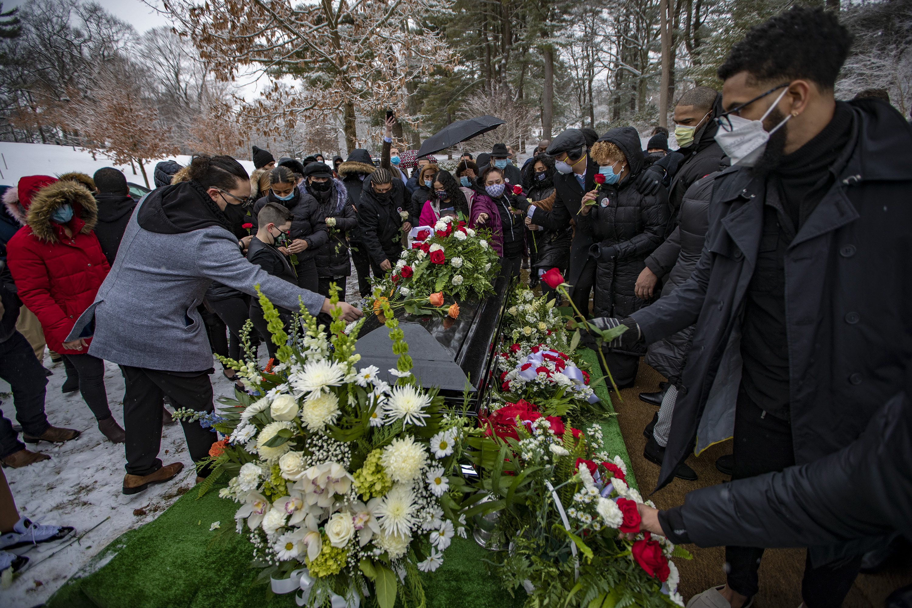 Friends and family place flowers on top of Henry Tapia's casket at Forest Hills Cemetery. (Jesse Costa/WBUR)