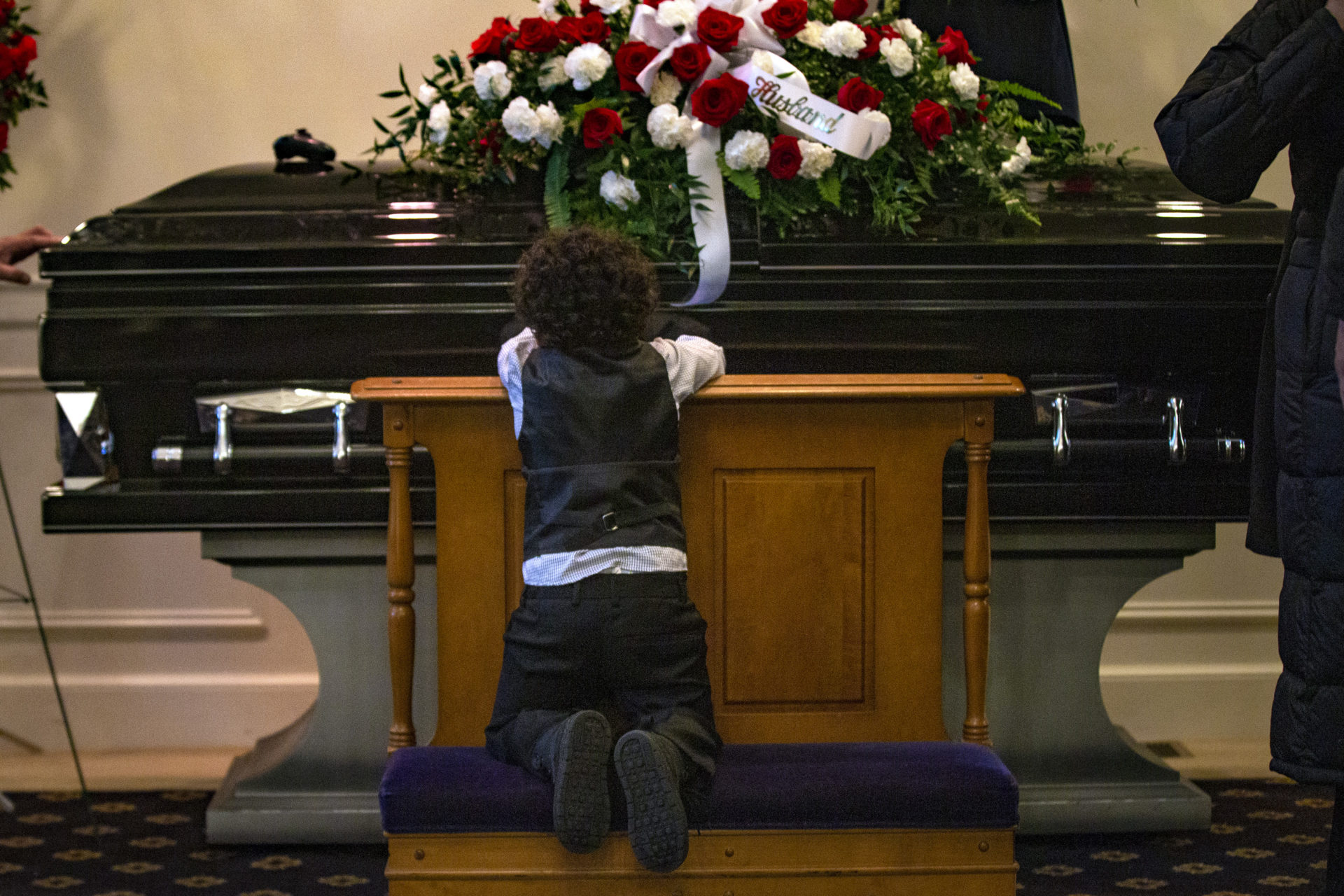 Three-year-old Eli kneels in front of his father's coffin.  (Jesse Costa / WBUR)