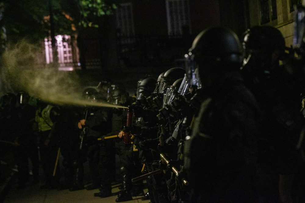 Boston Police lined up in Boston Common after protests on May 31 and deploy pepper spray toward protesters. (Jesse Costa/WBUR)