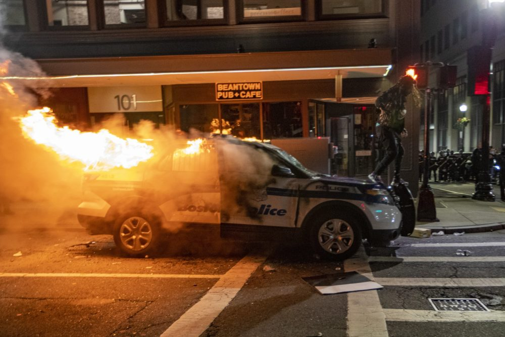 A protester walks on a Boston Police SUV set fire on Tremont Street after a protest for racial justice near the Massachusetts State House on May 31. (Jesse Costa/WBUR)