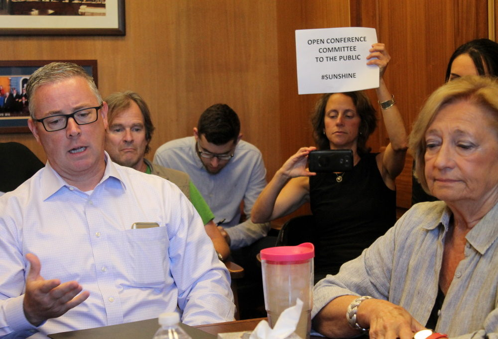 """Emily Norton, then-director of the Sierra Club Massachusetts Chapter, held up a sign July 19, 2018 promoting """"sunshine"""" and calling for members of a clean energy conference committee, including Reps. Thomas Golden and Patricia Haddad (foreground), to keep their talks open to the public rather than entering executive session. (Sam Doran/SHNS File)"""