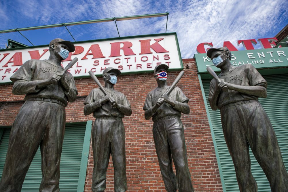 The statues of Ted Williams, Bobby Doerr,  Johnny Pesky and Dom Dimaggio wear masks outside of Fenway Park. (Jesse Costa/WBUR)