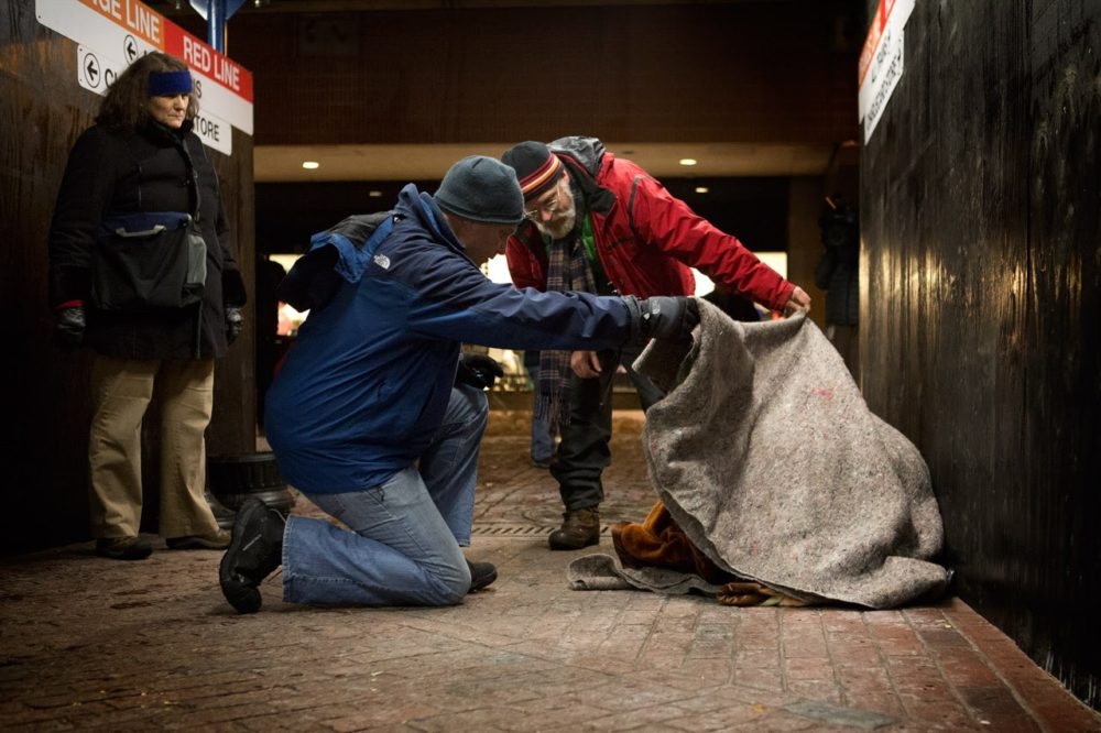 In this photo from 2013's homeless census, Jim Greene, then the director of the emergency shelter commission for the Boston Public Health Commission (in red), and a volunteer lift a blanket off of a woman at Downtown Crossing to check if she is okay. (Jesse Costa/WBUR)