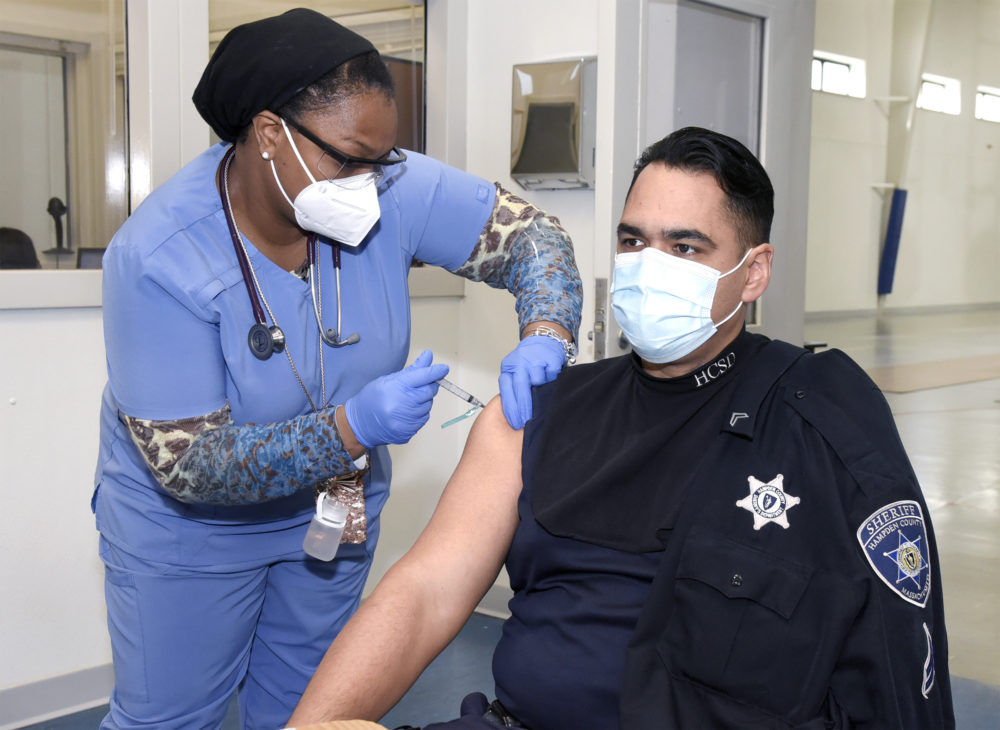 A Hampden County Sheriff's Department employee is given the vaccine by members of the department's medical team. (Courtesy Mark M.Murray/Hampden County Sheriff's Department)