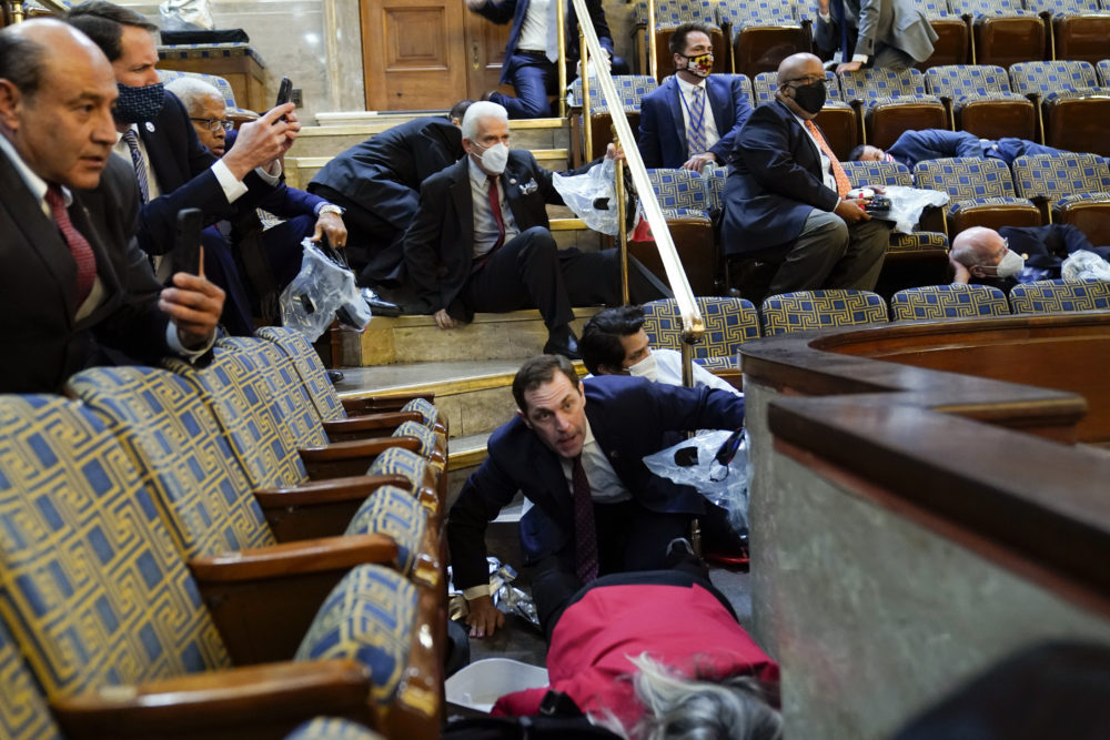 People shelter in the House gallery as protesters try to break into the House Chamber at the U.S. Capitol on Wednesday, Jan. 6, 2021, in Washington. (Andrew Harnik/AP)