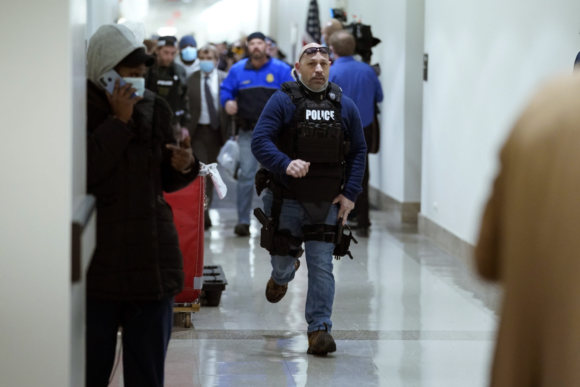 People run in the halls as protesters try to break into the House Chamber. (Andrew Harnik/AP)