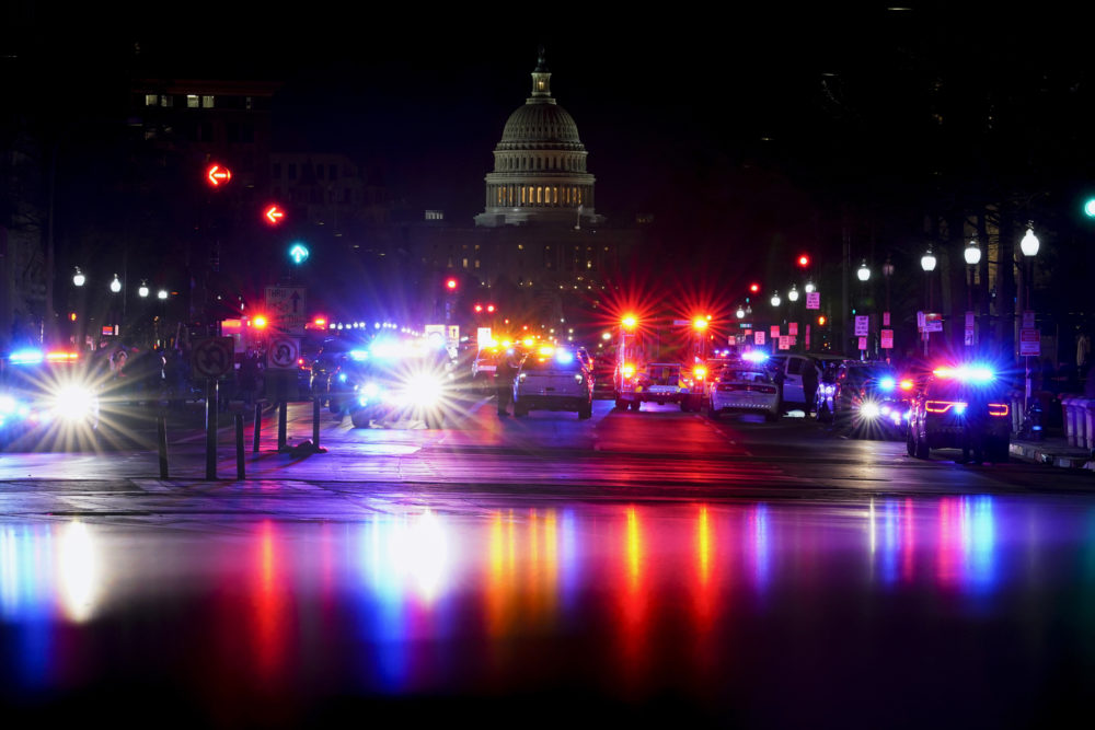 With the U.S. Capitol in the background, lights from police vehicles illuminate Pennsylvania Avenue in Washington, Wednesday, Jan. 6, 2021. (AP Photo/Carolyn Kaster)