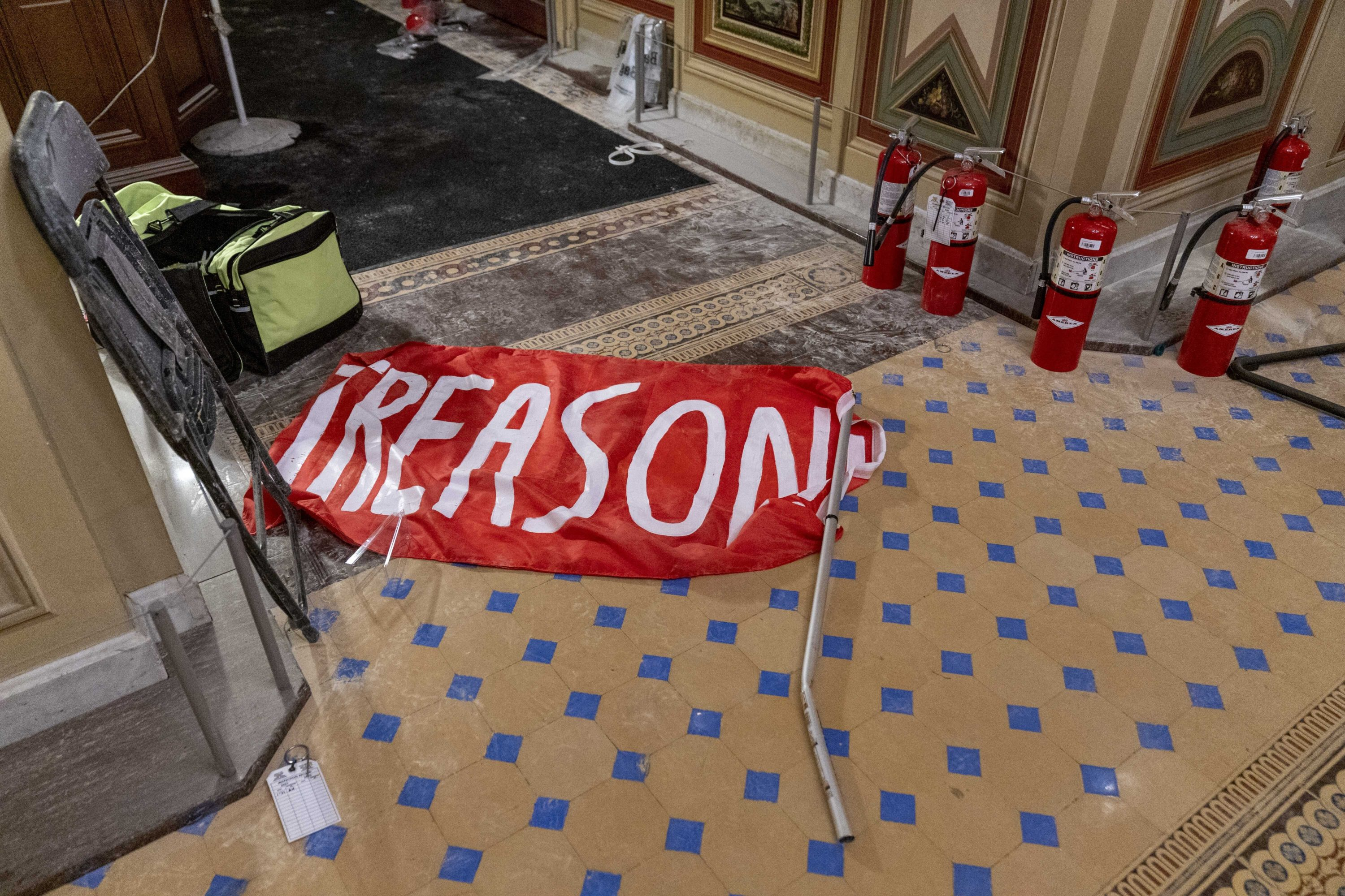 """A flag that reads """"Treason"""" is visible on the ground in the early morning hours of Thursday, Jan. 7, 2021, a day after protesters stormed the Capitol in Washington. (Andrew Harnik/AP)"""
