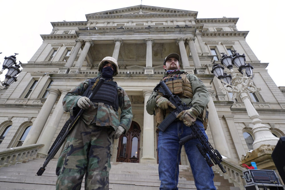 In this Jan. 6, 2021 file photo, armed men stand on the steps at the State Capitol after a rally in support of President Donald Trump in Lansing, Mich.  (AP Photo/Paul Sancya, File)