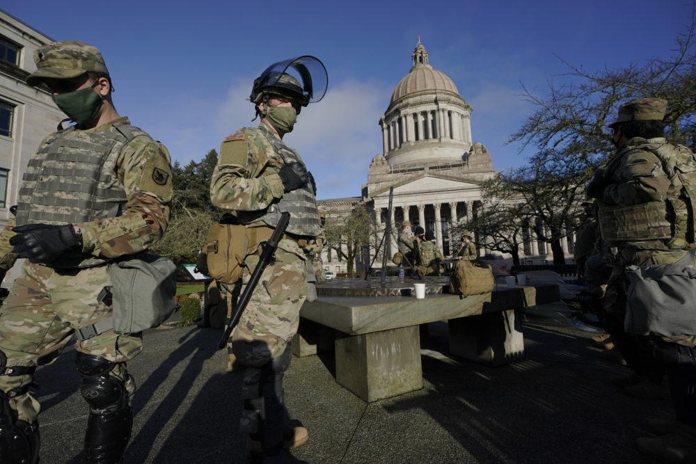 Members of the Washington National Guard stand at a sundial near the Legislative Building, Sunday, Jan. 10, 2021, at the Capitol in Olympia, Wash. Governors in some states have called out the National Guard, declared states of emergency and closed their capitols over concerns about potentially violent protests. (Ted S. Warren/AP)