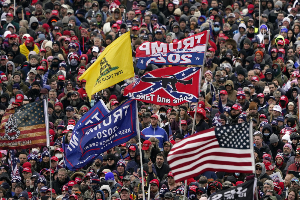 Supporters listen as former President Trump speaks as a Confederate-themed and other flags flutter in the wind during a rally in Washington on Jan. 6. (Evan Vucci/AP)