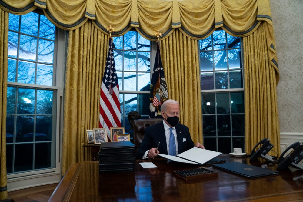 President Joe Biden signs a series of executive orders in the Oval Office on Wednesday night. (Evan Vucci/AP)