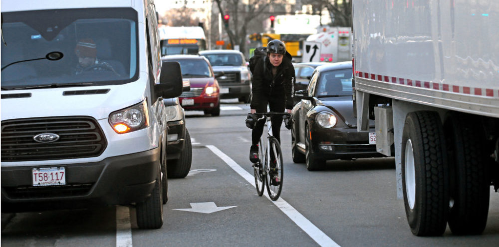 Vehicles block part of a bike lane on Main Street in Cambridge, MA, causing a bicyclist to compete with traffic, on Jan. 25, 2019. (David L. Ryan/The Boston Globe via Getty Images)