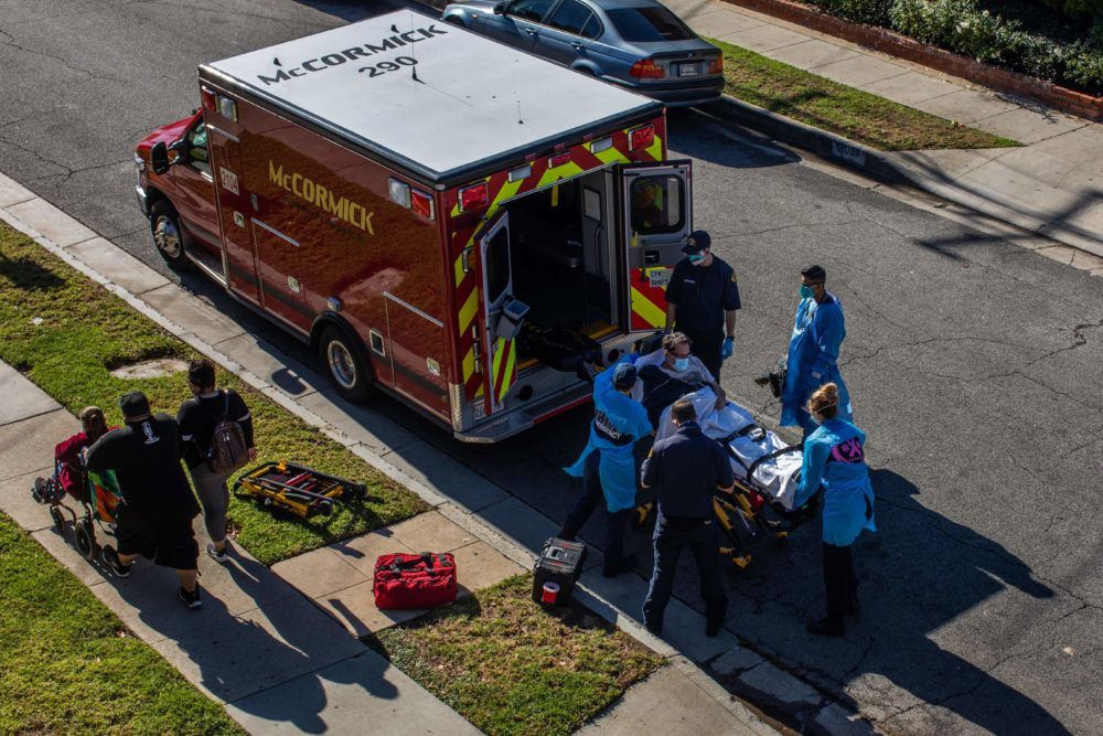 After administering him with oxygen, County of Los Angeles paramedics load a potential COVID-19 patient in the ambulance before transporting him to a hospital in Hawthorne, California on Dec. 29, 2020 as a family walks by. (Apu Gomes/AFP via Getty Images)
