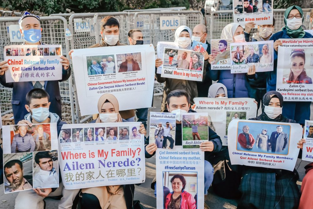 Members of the Muslim Uighur minority hold placards as they demonstrate in front of the Chinese consulate on December 30, 2020, in Istanbul, to ask for news of their relatives. (Bulent Kilic/AFP via Getty Images)
