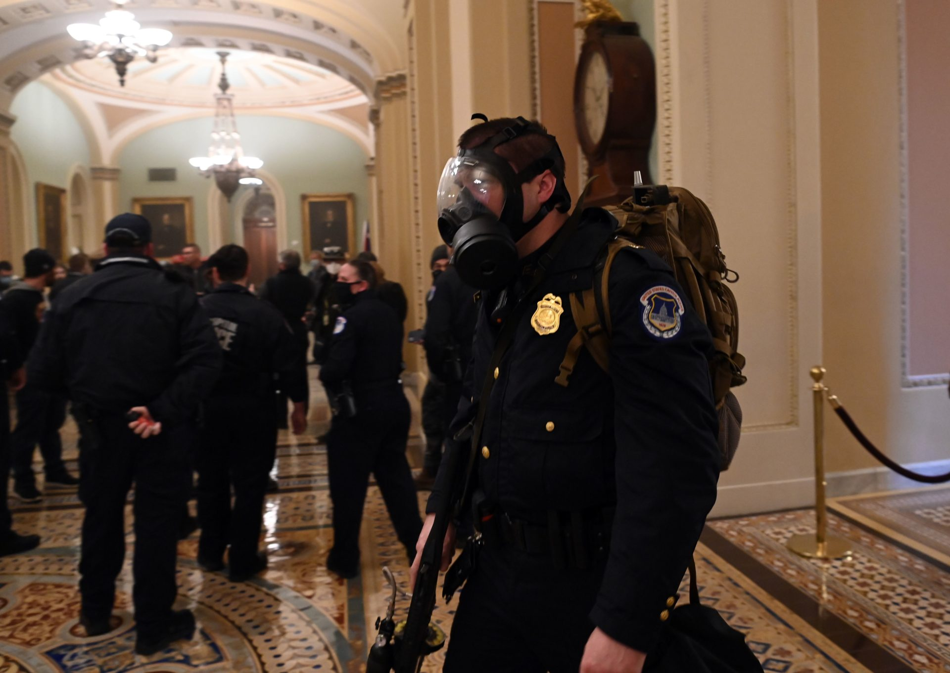 A U.S. Capitol police officer wears a gas mask as supporters of US President Donald Trump enter the Capitol on Jan. 6, 2021, in Washington, D.C. (Saul Loeb/AFP via Getty Images)