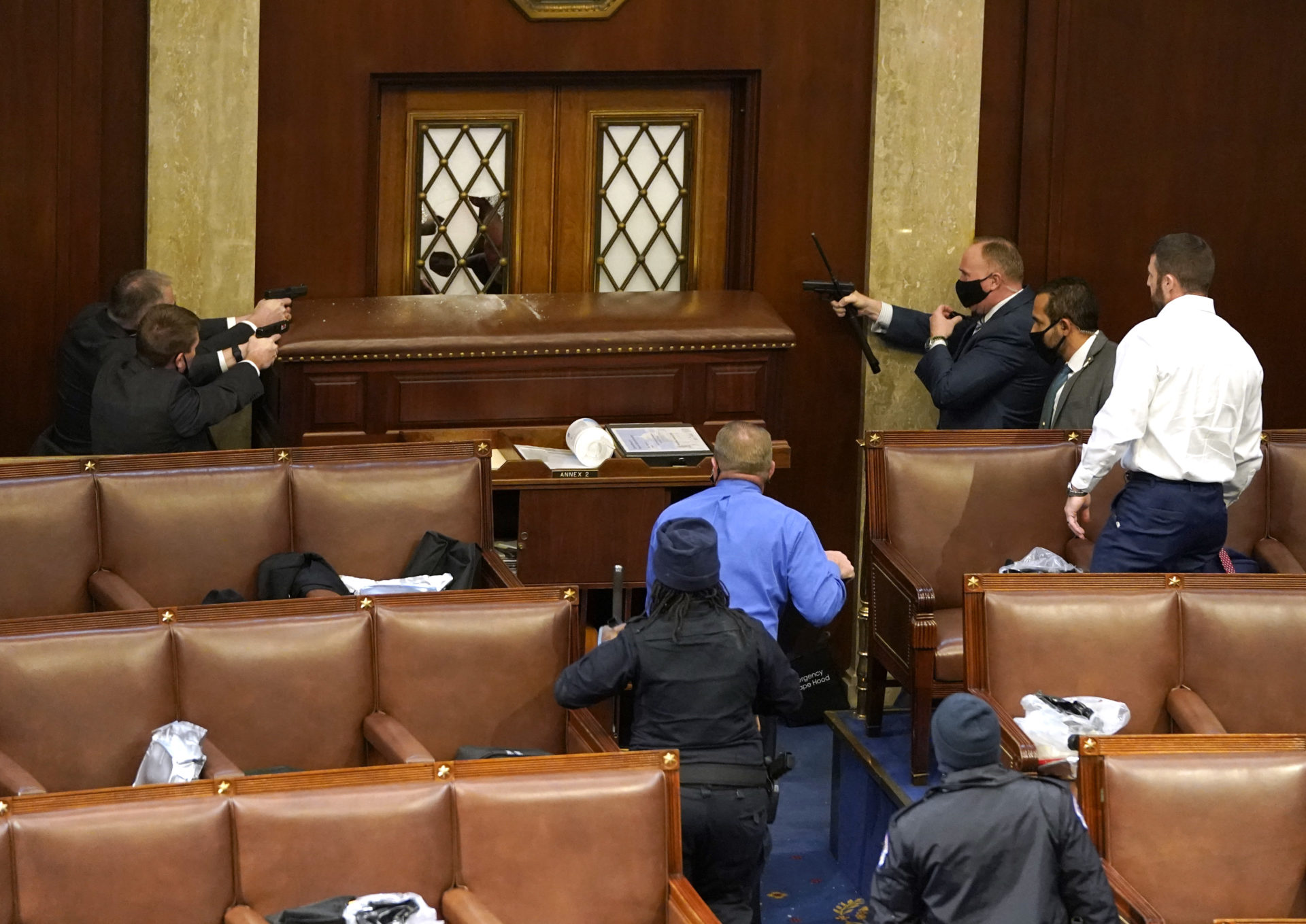 Capitol police officers point their guns at a door that was vandalized in the House Chamber during a joint session of Congress on Wednesday. (Drew Angerer/Getty Images)