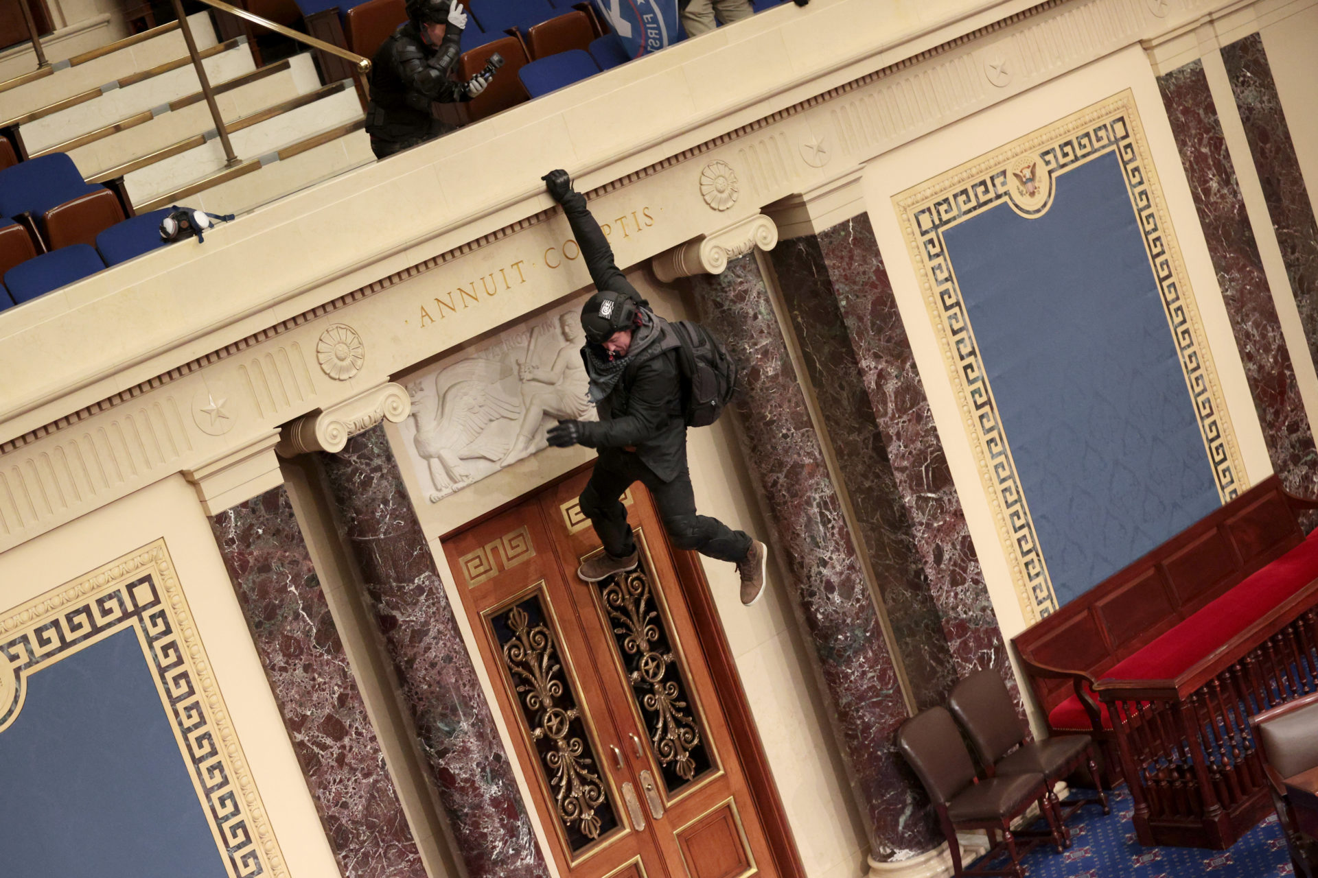 A protester is seen hanging from the balcony in the Senate Chamber. (Win McNamee/Getty Images)