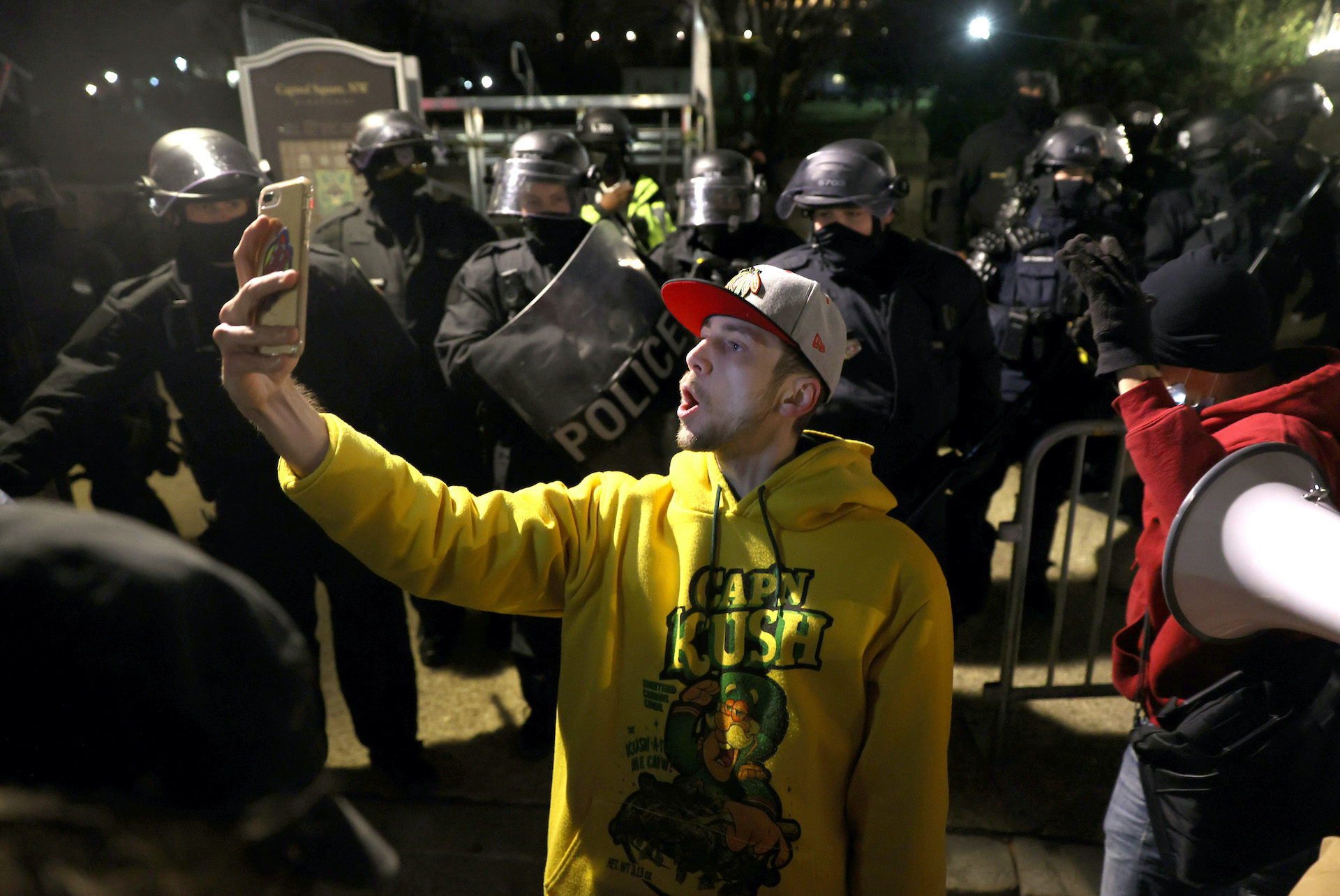 A protester takes a photo with police officers in riot gear dispersing protesters gathering at the U.S. Capitol Building. (Tasos Katopodis/Getty Images)