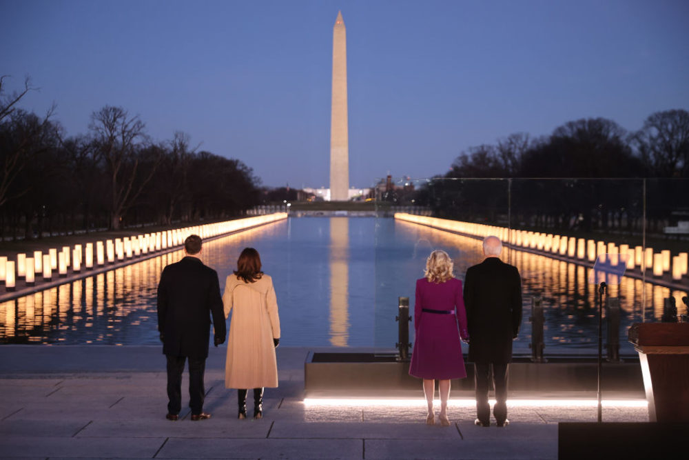 (L-R) Douglas Emhoff, Vice President Kamala Harris, Dr. Jill Biden and President Joe Biden look down the National Mall as lamps are lit to honor the nearly 400,000 American victims of the coronavirus pandemic at the Lincoln Memorial Reflecting Pool January 19, 2021 in Washington, DC. (Chip Somodevilla/Getty Images)
