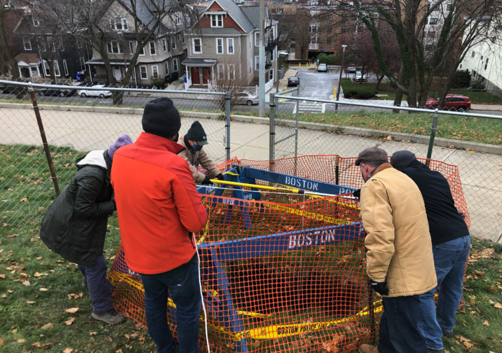 A team of researchers on Dec. 8, lowering a camera rig (an iPhone and some flashlights tied to a paint roller) into the sinkhole. (City of Boston Archaeology Program)