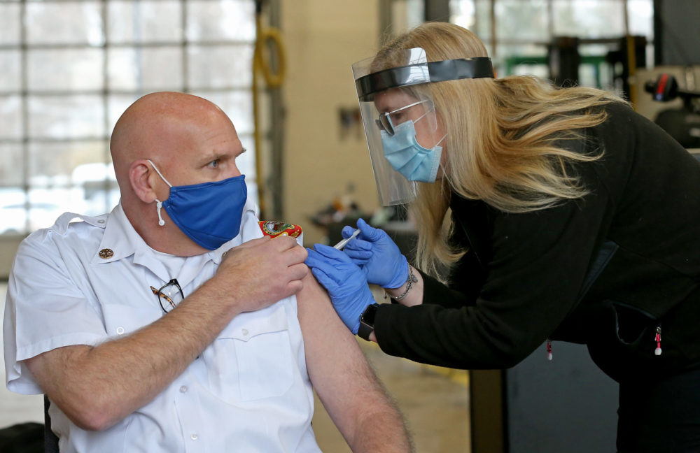Norwood Fire Chief George Morrice receives a COVID-19 vaccine from registered nurse Stacey Lane on January 11, 2021 in Norwood, Massachusetts.   (Matt Stone/Boston Herald via Getty Images)
