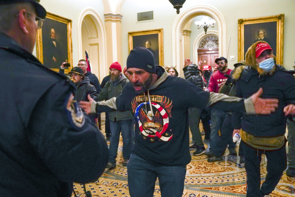 Trump supporters gesture to U.S. Capitol Police in the hallway outside of the Senate chamber at the Capitol in Washington, Wed., Jan. 6, 2021. (Manuel Balce Ceneta/AP)