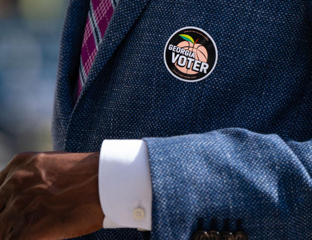 "A ""Georgia Voter"" sticker is seen on the jacket of Democratic U.S. Senate candidate Raphael Warnock after he cast his ballot during early voting on October 21, 2020 in Atlanta, Georgia. (Elijah Nouvelage/Getty Images)"