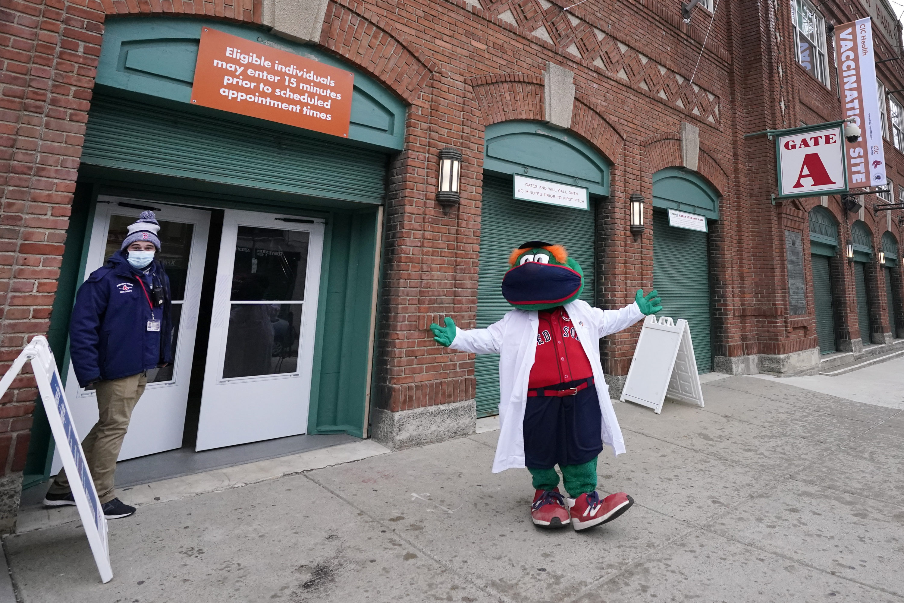 Boston Red Sox mascot, Wally the Green Monster, gestures while dressed in a medical white coat outside Fenway Park, Monday Feb. 1, 2021, in Boston. Fenway Park is one of several large COVID-19 vaccination sites in the Boston area. (Elise Amendola/AP)