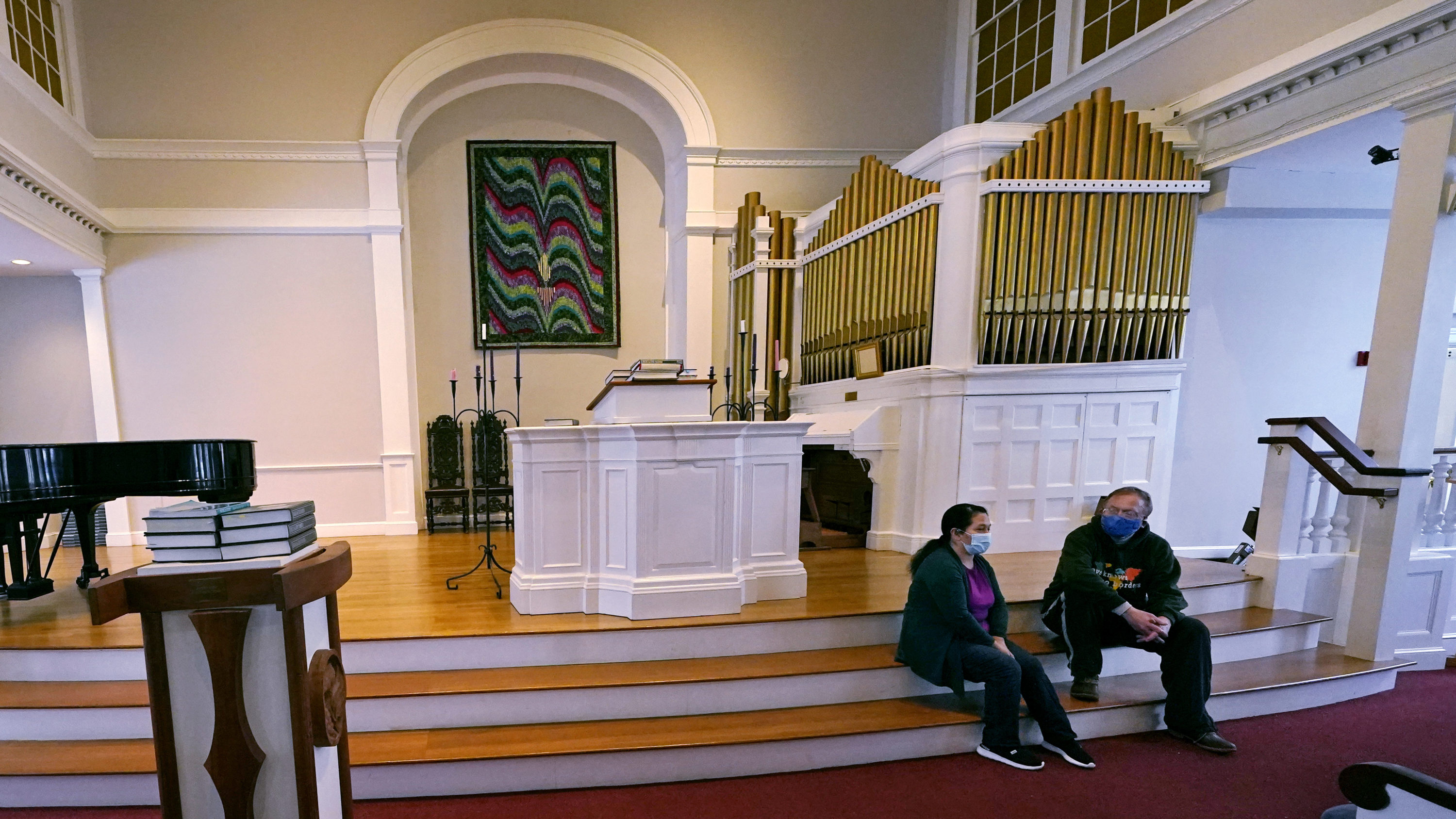 Maria Macario, left, talks with Rev. John Gibbons while seated on the steps to the altar at the First Parish church in Bedford. (Charles Krupa/AP)