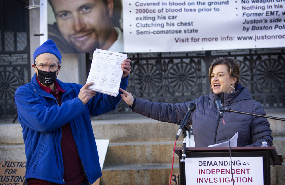 Holding a copy of a petition demanding an independent investigation into Juston Roots's shooting death, Juston Root's father Evan Root and sister Jennifer Root-Bannon addressed a crowd during a rally outside of the Massachusetts State House on Friday. (Robin Lubbock/WBUR)