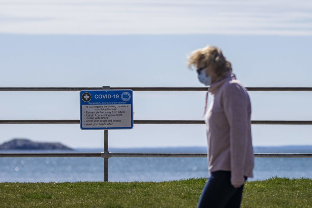 A woman walks past a sign at King's Beach in Swampscott listing the CDC recommendations for social gathering during the pandemic in April 2020. (Jesse Costa/WBUR)