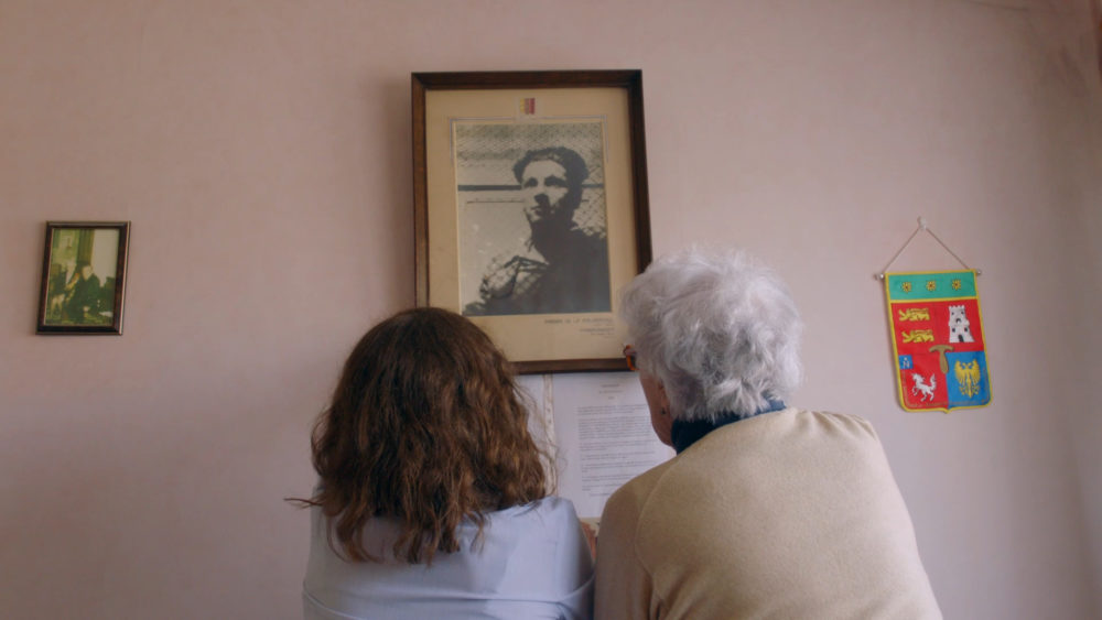 Colette Marin-Catherine (right) and Lucie Fouble look at a picture of Marin-Catherine's brother, Jean-Pierre, who died in the Mittelbau-Dora concentration camp in Germany. (Courtesy of The Guardian)