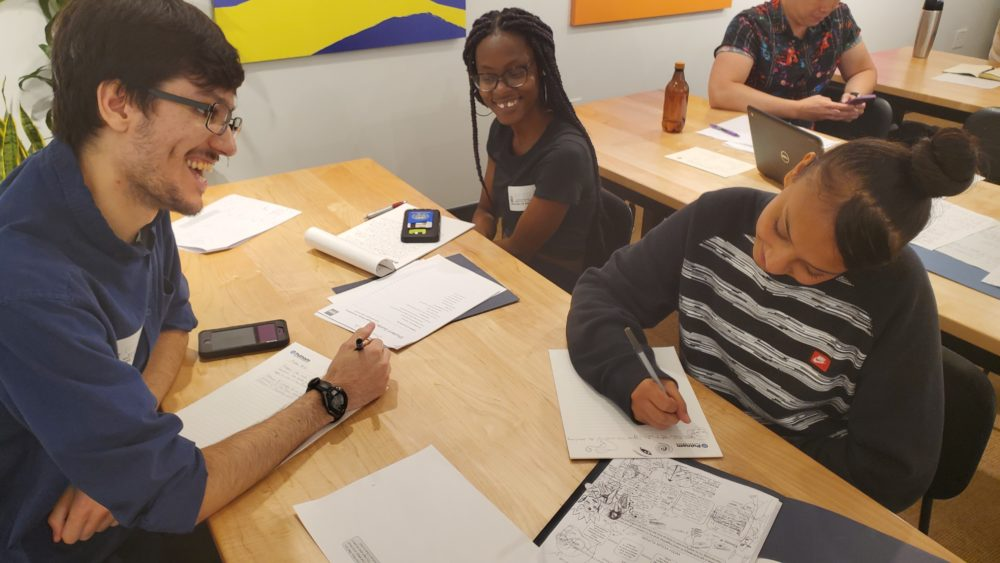 826 Boston Writers' Room coordinator Richie Wheelock (left) works with students at Boston International Newcomers Academy on their personal statements. (Courtesy 826 Boston)