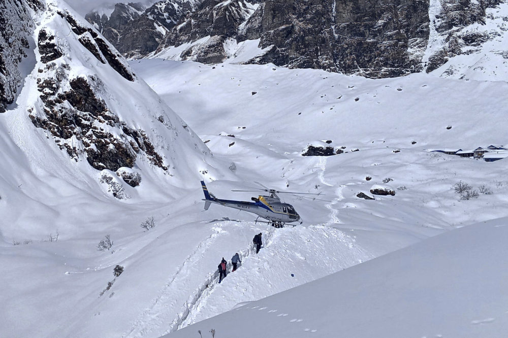 In this Jan. 18, 2020 photo, trekkers are being rescued in a helicopter a day after an avalanche hit Mount Annapurna trail in Nepal. (Phurba Ongel Sherpa/AP)