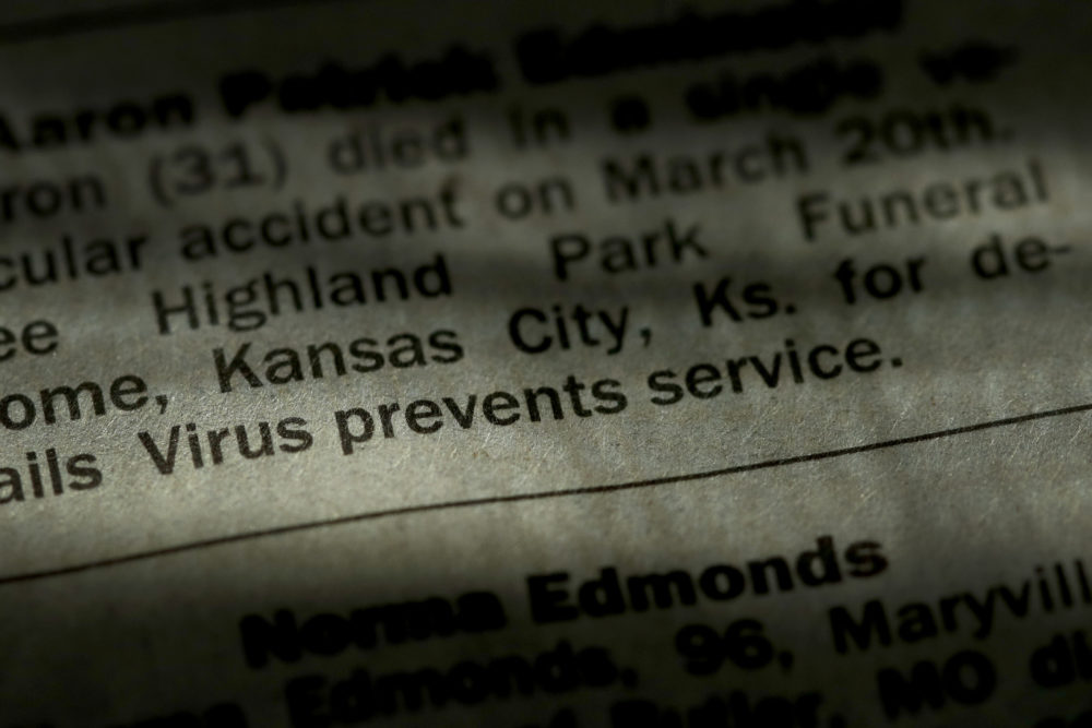 An obituary in the Kansas City Star newspaper details the effect of the COVID-19 pandemic on traditional funeral services, Sunday, April 5, 2020, in Overland Park, Kan. Most funerals now are either small private services with a public memorial service sometime in the distant future or no public service at all in response to social distancing and stay-at-home orders implemented in an effort to stem the spread of the new coronavirus. (Charlie Riedel/AP)