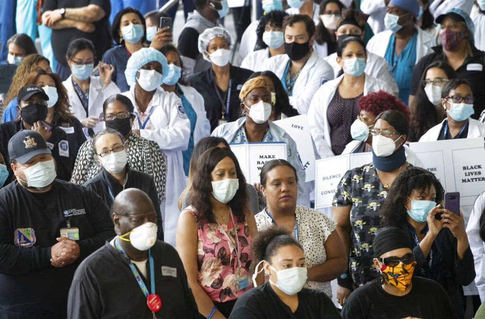 Health care workers at Brooklyn's Kings County Hospital show their solidarity with the Black Lives Matter movement, Thursday, June 4, 2020 in New York during the coronavirus pandemic. (AP Photo/Mark Lennihan)