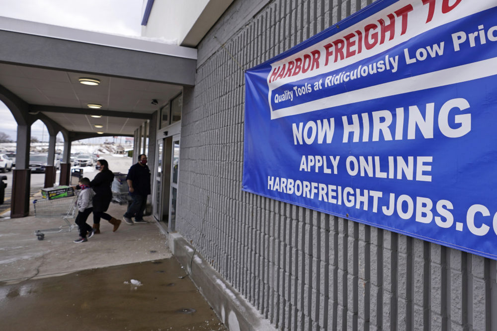 "In this Dec. 10, 2020 file photo, a ""Now Hiring"" sign hangs on the front wall of a Harbor Freight Tools store in Manchester, N.H.   (Charles Krupa/AP File)"