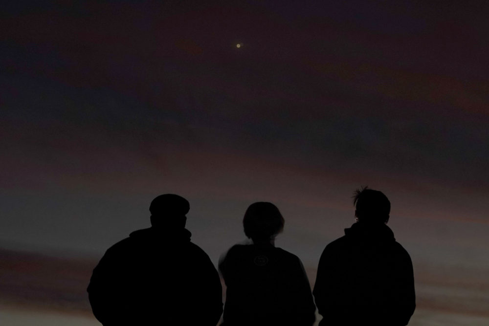 People are silhouetted against the sky at dusk as they watch the alignment of Saturn and Jupiter, Monday, Dec. 21, 2020, in Edgerton, Kansas. (Charlie Riedel/AP)