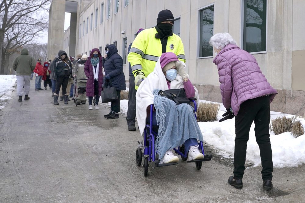 People wait in line for a coronavirus vaccine in Wakefield Monday. (Elise Amendola/AP)