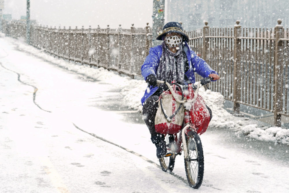 A woman rides a bicycle across the Brooklyn Bridge during a snowstorm, Sunday, Feb. 7, 2021, in Brooklyn. It was the second time in less than a week the area has been buffeted by heavy snowfall. (Kathy Willens/AP)