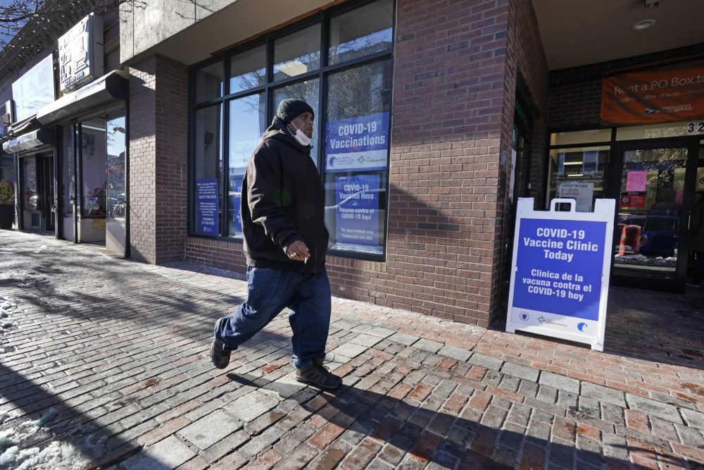 A man walks by the recently opened COVID-19 vaccination site in Chelsea, Feb. 8, 2021. Chelsea's vaccination sites are limited by Massachusetts' eligibility rules. (Elise Amendola/AP)