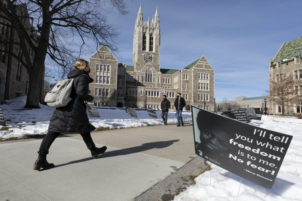 Students walk past Black History Month posters on the Boston College campus, Wednesday, Feb. 17, 2021, in Boston. Harassment by white male students targeting Black and Latina women housed in a Boston College dormitory has revived concerns about racism on campus. (Michael Dwyer/AP)