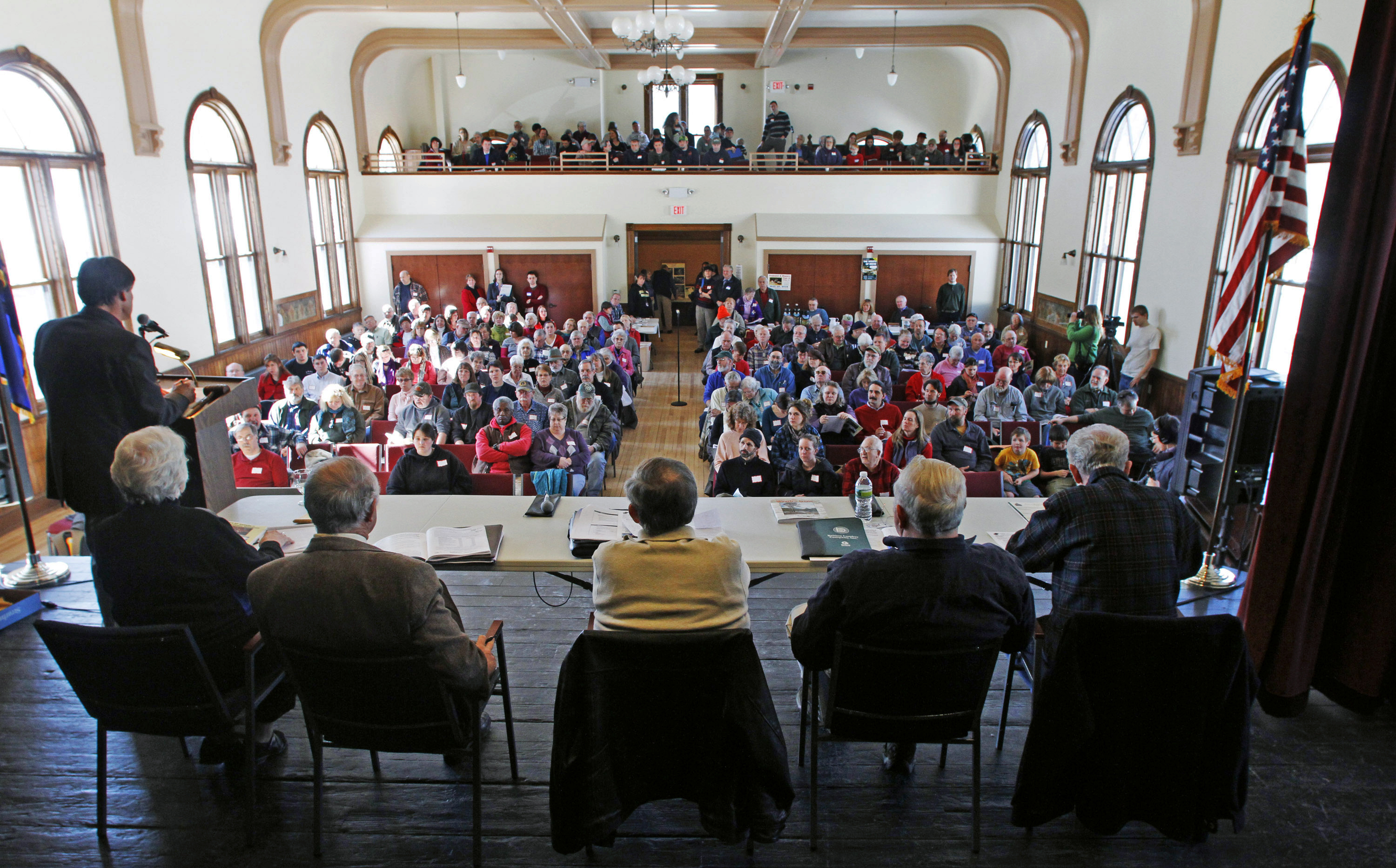 In this March 6, 2012, file photo, officials preside over the annual town meeting in Bethel, Vt. The COVID-19 pandemic is disrupting New England town meetings in 2021, a tradition where citizens gather to debate and decide on local issues. (Toby Talbot/AP File)