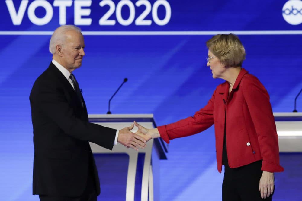 In this Feb. 7, 2020 file photo, Joe Biden and Elizabeth Warren shake hands on stage before the start of a Democratic presidential primary debate. (Charles Krupa/AP)