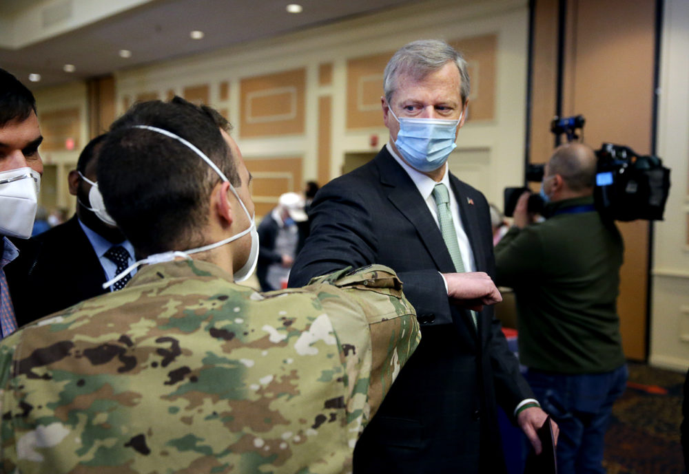 Senior Airman William Borcy, left, greets Gov. Charlie Baker during a tour of the mass vaccination site at the DoubleTree by Hilton Hotel Boston North Shore in Danvers on Feb. 10, 2021. (Jonathan Wiggs/The Boston Globe via Getty Images)