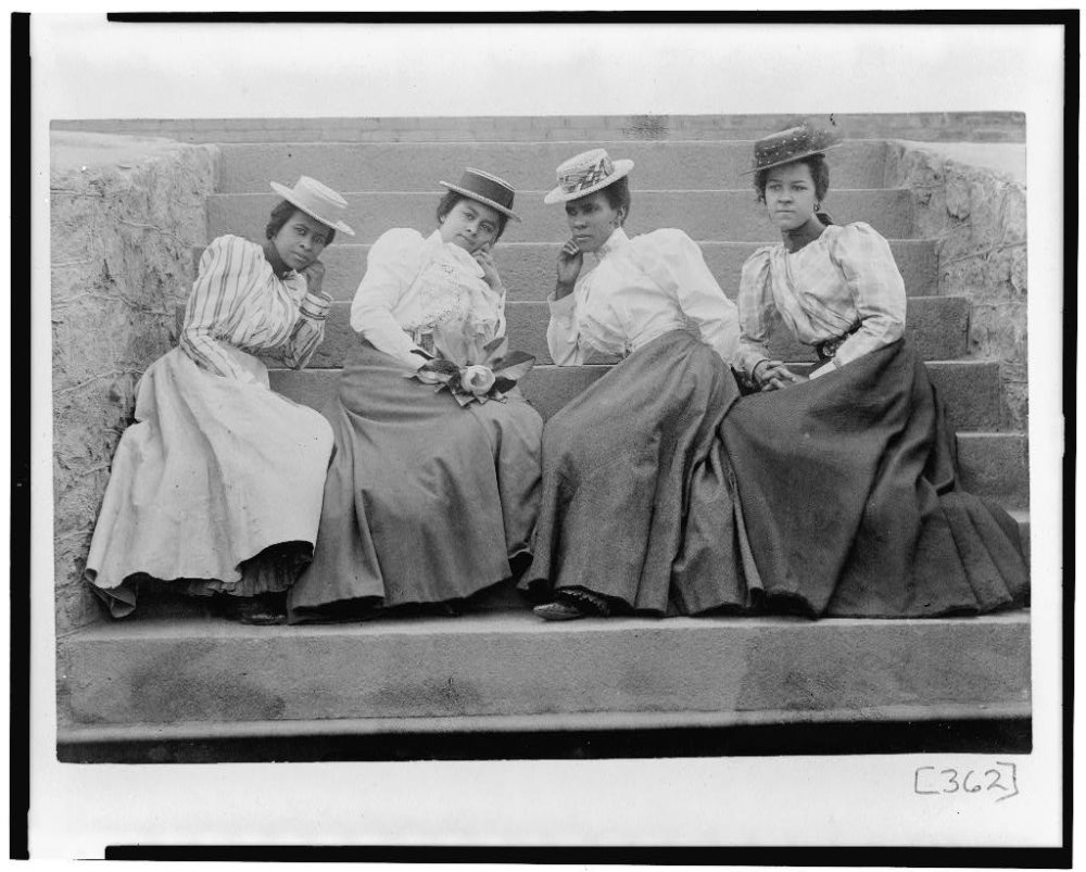 """Four African American women seated on steps of building at Atlanta University, Georgia. This picture is part of W.E.B. Du Bois award-winning """"Exhibit of American Negroes."""" (Courtesy of Library of Congress Prints and Photographs Division.)"""