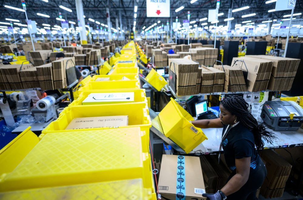 A woman works at a packing station in Amazon's fulfillment center in Staten Island. (Johannes Eisele/AFP via Getty Images)